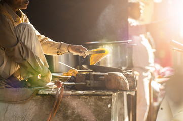 An Indian elderly man is cooking Chapati on the streets of Jaipur, Rajasthan, India. Chapati is an unleavened flatbread originating from the Indian subcontinent.