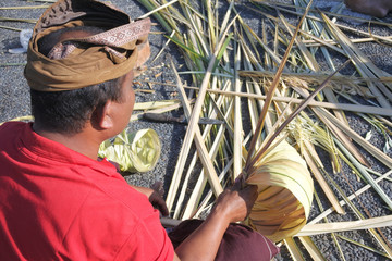Balinese man preparing Traditional Bali Penjor bamboo pole  in Bali Indonesia