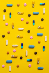 Various types of pills on yellow background