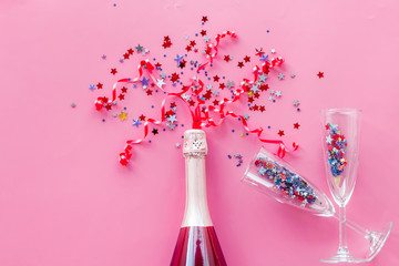 Champagne bottle with glasses and colorful party streamers for celebration on pink background top view