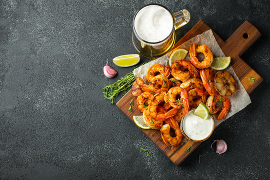 Grilled shrimps or prawns served with lime, garlic and white sauce on a dark concrete background. Seafood. Top view with copy space. Flat lay