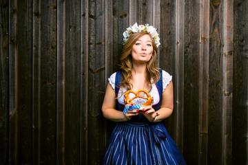 Frau im Dirndl vor Holzhintergrund Oktoberfest Theme