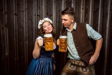 Mann und Frau in traditionellen bayerischen trachten kleidung Trinken Bier und lachen