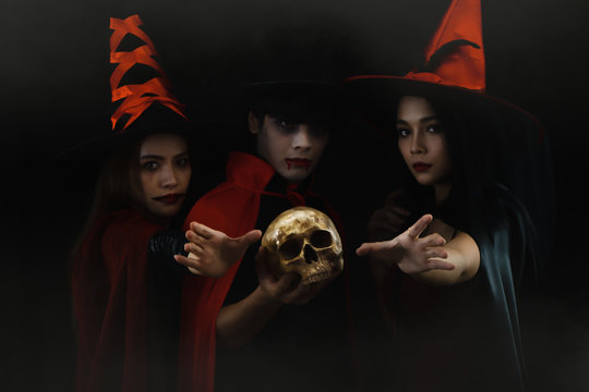 halloween portrait on dark background of man in vampire costume with two women in witch costume for halloween party with human skul in misty atmosphere