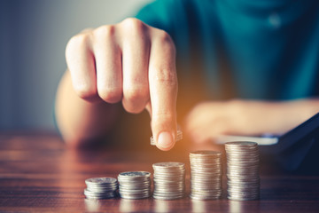 Hand putting money coin on each line rising - business saving money concept  for finance accounting