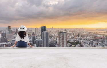 Wall Mural - Woman in white hat sitting on building terrace, looking at city in sunset
