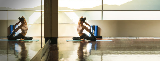 Skinny good looking asian woman practicing yoga alone in studio room with reflection in mirror Wall mural