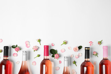 Composition with bottles of delicious rose wine on white background, top view