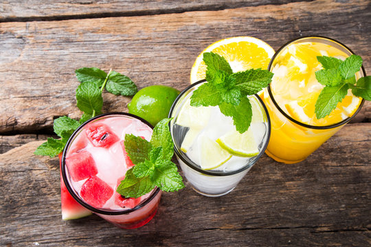 Glasses of lime, orange and water melon soda drinks on wooden background
