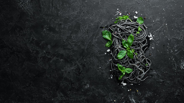Black pasta with basil. On a black stone background. Top view. Free copy space.