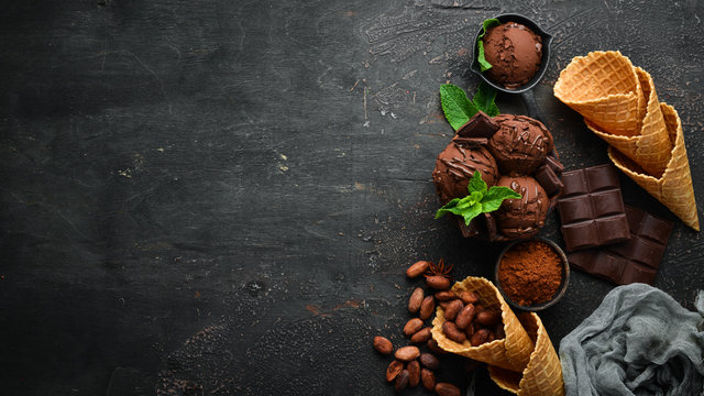 Ice cream with chocolate. Making ice cream on Wooden background. Top view. Free space for your text.
