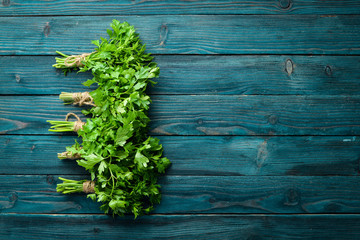 Fototapete - Fresh parsley on a wooden background. Top view. Free space for your text.