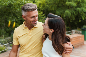 Portrait of smiling middle-aged couple looking at each other and hugging while walking in summer park