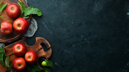 Fresh red apples with green leaves on a black background. Fruits. Top view. Free space for text. Fototapete