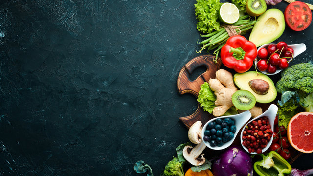 Fresh vegetables and fruits on a black background. Vitamins and minerals. Top view. Free space for your text.