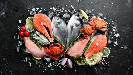 Deurstickers Schaaldieren Seafood: Dorado, salmon, crab, grouper, oysters. On a black stone background. Top view. Free space for your text.