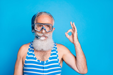 Close up photo of attractive man showing ok sign wearing snorkel gear striped bathing suit isolated over blue background