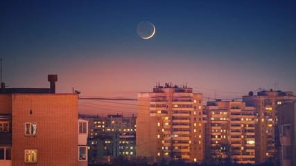 Fotobehang - Beautiful waxing crescent moon setting behind city skyline buildings rooftops at night. Timelapse, 4K UHD.