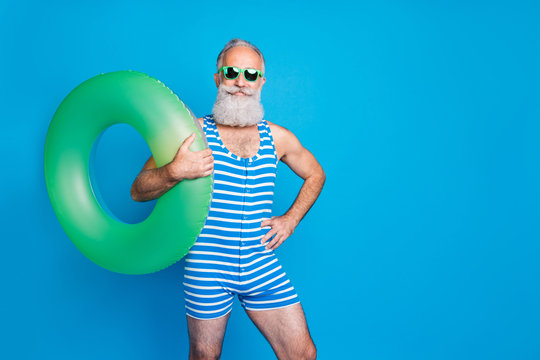 Portrait of confident man in eyeglasses eyewear holding green toy circle wearing striped swim wear isolated over blue background