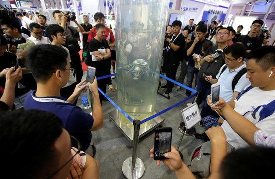 Visitors look at a robotic jellyfish swimming in a water tank at Festo's booth at the World Robot Conference in Beijing
