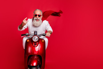 Portrait of funky pensioner in eyewear eyeglasses showing rock-and-roll sign driving bike wearing white jumper isolated over red background Fotoväggar