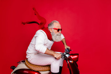 Elderly santa man moving fast to party by vintage moped wear white jumper and trousers isolated red background Fototapete