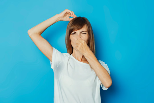 Young girl in a white T-shirt with wet armpits from sweat on a blue background. Concept of excessive sweating, heat, deodorant