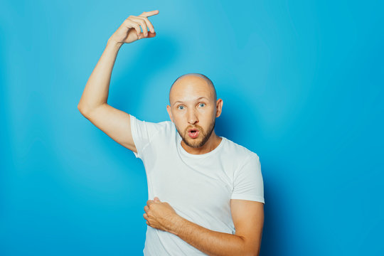 Young man in a white T-shirt with wet armpits from sweat on a blue background. Concept of excessive sweating, heat, deodorant