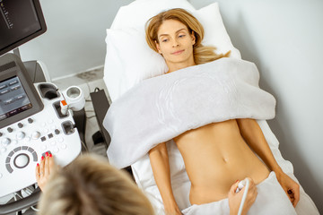 Woman examining her abdomen with ultrasound