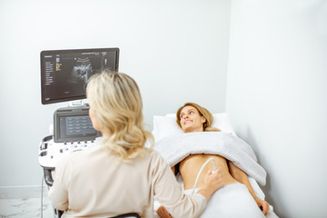 Doctor performs ultrasound examination of a woman