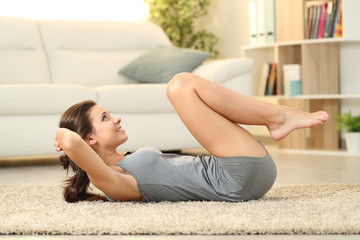 Girl doing crunches on a carpet at home