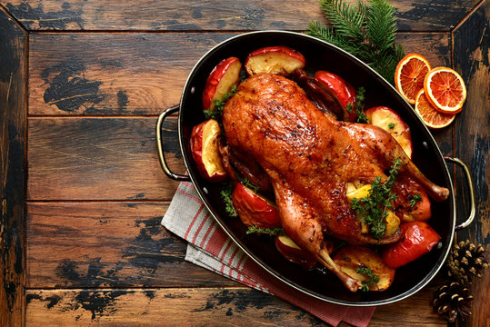 Roast goose stuffed with baked apples in a skillet, festive christmas recipe. Top view with copy space.
