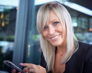 Hübsche Junge Frau mit Smartphone im Cafe