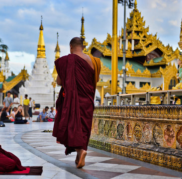 buddhist pilgrims dressed in red traditional robes praying in the golden temple in myanmar