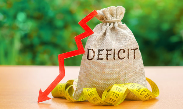 Money bag with the word Deficit and tape measure with down arrow. Budget deficit concept. Low profit. Financial costs. Bankruptcy. Adverse conditions in foreign markets. Capital outflow