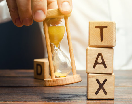 Businessman's hand holding a hourglass near the wooden blocks with the word Tax. Time to pay taxes. The concept of annual taxation. Taxes on vehicles, property, purchases, luxury. State fee