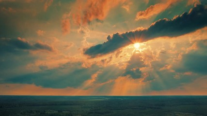 Fotobehang - Aerial view of sun shining through clouds in dramatic sunset sky over forest landscape. Hyperlapse timelapse, 4K UHD.