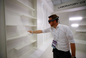 A gamer grabs for a virtual book from an empty shelf as he wears augmented reality goggles during the media day of Europe's leading digital games fair Gamescom, which showcases the latest trends of the computer gaming scene, in Cologne