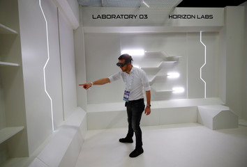 A gamer points to a virtual item in an empty room as he wears augmented reality goggles during the media day of Europe's leading digital games fair Gamescom, which showcases the latest trends of the computer gaming scene, in Cologne