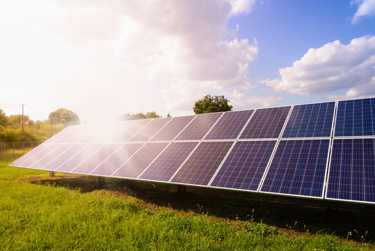 Solar panels mounted on the ground. Green grass and sunny blue sky background