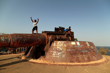 Woman poses for pictures while standing on an old French gun emplacement at Goree Island off the coast of Dakar