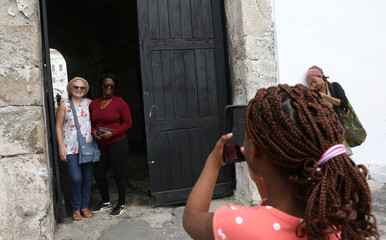 American tourist, Divine Koufahenou takes a picture of her Mother Afi and her friend Dawn Kravig at the 'Door of No Return' at the Cape Coast Slave Castle