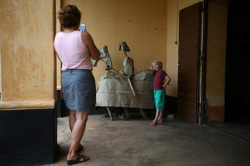 Woman takes a picture of a boy posing with a metal sculpture at the Da-Silva Museum in Porto-Novo