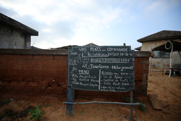 Sign advertising food and tourism services is seen at a closed down hotel near the monument at the 'Point of No Return' at the historic slave port of Ouidah, Benin