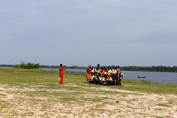 School children on a field trip pose for a group photograph on the beach at the slave port in Badagry