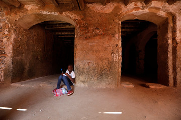 Schoolgirl takes notes as she prepares her presentation during her school's visit at the 'Maison Des Esclaves' slaves' house, at Goree Island off the coast of Dakar