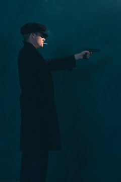 Retro mobster with cigarette shoots with gun. Side view.