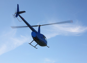 The aircraft - Blue small helicopter makes flight low  height