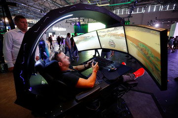 A gamer plays a car racing game during the media day of Europe's leading digital games fair Gamescom, which showcases the latest trends of the computer gaming scene, in Cologne