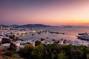 Panorama von Mykonos Stadt und altem Hafen während eines farbenfrohen Sonnenunterganges im Sommer, Kykladen, Griechenland